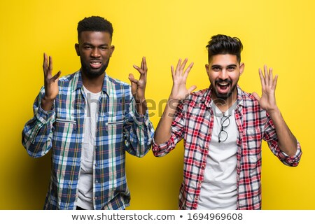 Image of young man 20s wearing casual t-shirt screaming and rais Stock photo © deandrobot
