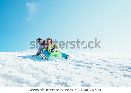 family enjoying sledging down snowy hill stock photo © monkey_business