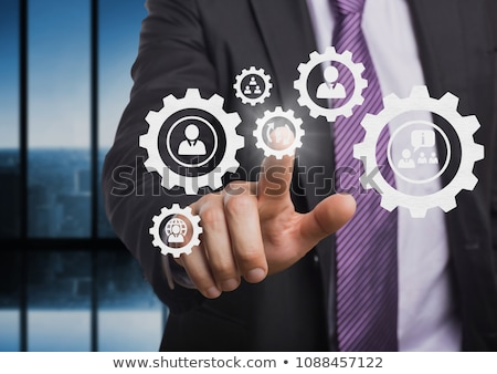 Business man interacting with people in cogs graphics against blue background Stock photo © wavebreak_media