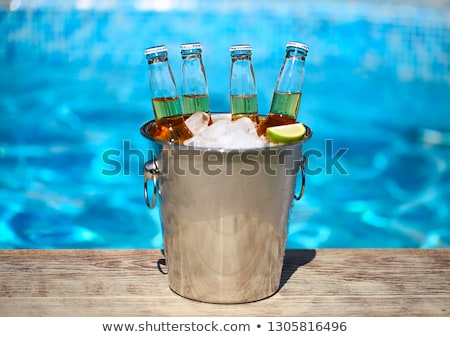 Closeup view of bucket with ice cubes, beer bottles and lime sli Stock photo © dashapetrenko