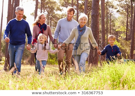 Front view of happy multi-generation family holding hands and walking on beach in the sunshine Stock photo © wavebreak_media