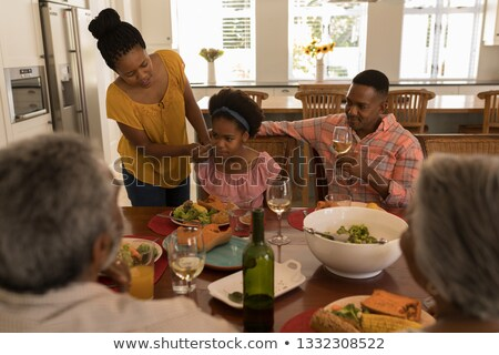 High angle view of an African American mother wiping daughters mouth with napkin after meal on dinin Stock photo © wavebreak_media