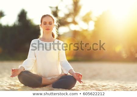 Yoga meditation woman meditating at beach sunset relaxing in yoga tree pose doing sun salutation. Re Stock photo © Maridav