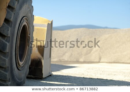 Tire backhoe close-up and piles of sand  Stock photo © deyangeorgiev