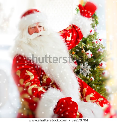 Santa sitting at the Christmas tree, near fireplace and looking  Stock photo © HASLOO