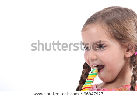 little girl eating a candy looked amused and impish stock photo © photography33
