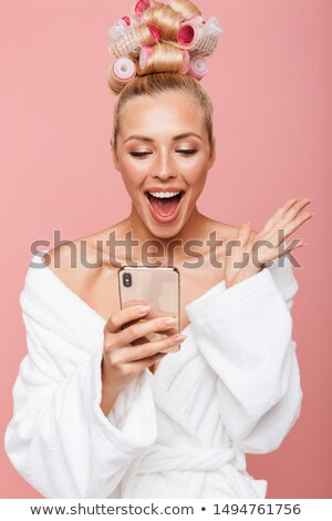 Young woman standing in bathrobe and celebrating success Stock photo © bmonteny