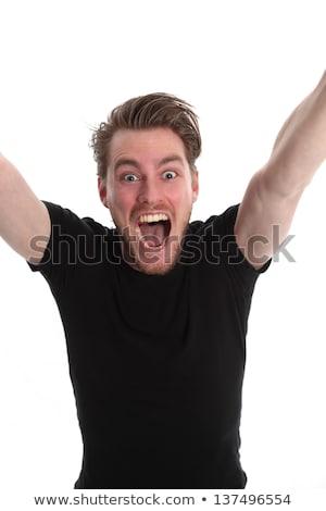 Sikeres férfi fekete póló tart ököl Stock fotó © feelphotoart
