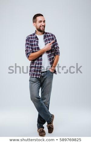Full length portrait of happy hipster in studio Stock photo © deandrobot
