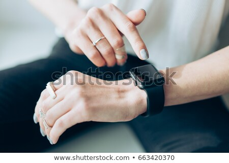 Slender girl with a smart clock on her arm Stock photo © tekso