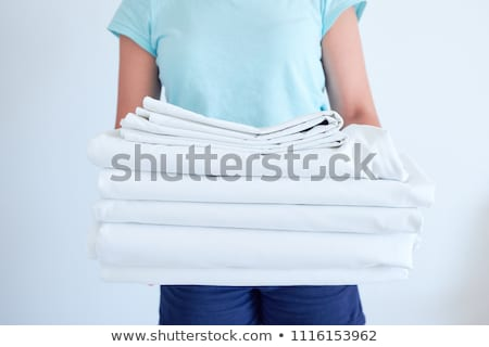 Cropped image of a hotel maid changing bed sheet Stock photo © deandrobot
