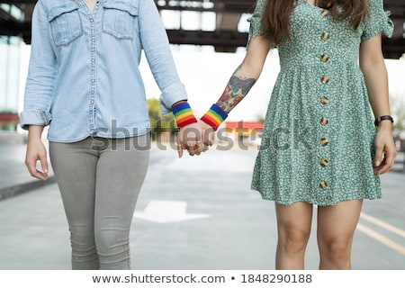 hands of couple with gay pride rainbow wristbands Stock photo © dolgachov
