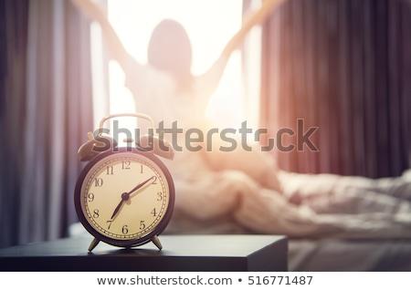 gyönyörű · barna · hajú · ébresztőóra · otthon · hálószoba · lámpa - stock fotó © lopolo