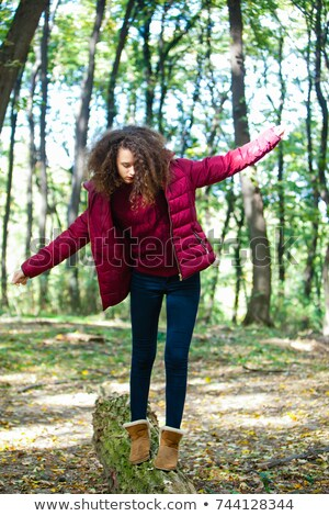 Teen girl walking down a fallen trunk in an autumn forest Stock photo © boggy