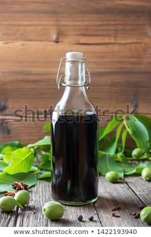 a bottle of homemade nut liqueur with walnuts stock photo © madeleine_steinbach