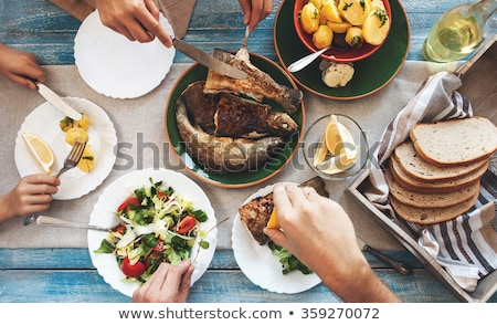 Food on table. Fish and bread on a plate with healthy vegetables. Ice tea and piece of bread on the  Stock photo © makyzz