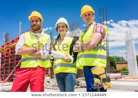 Portrait of three confident and reliable young employees at construction site Сток-фото © Kzenon