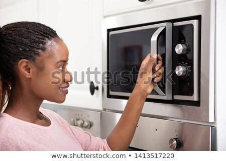 Afrikaanse vrouwen hand opening oven deur Stockfoto © AndreyPopov
