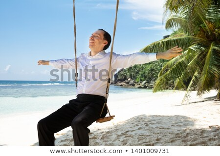 Young Man On Swing Enjoying The Fresh Air At Beach Stock photo © AndreyPopov