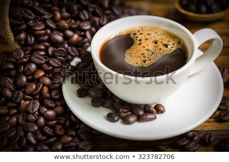 close up coffee cup and beans on wooden table stock photo © dolgachov