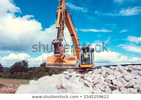 Woman operating an excavator on road works construction site Stock photo © Kzenon