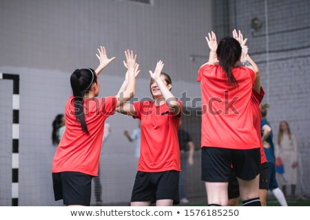 Team of active girls in sports uniform expressing triumph by high-five gesture Stock photo © pressmaster