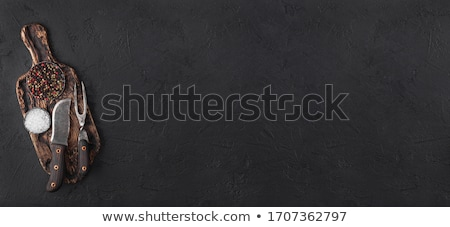 Stone chopping board with meat hatchets and fork with knife on black background with salt and pepper Stock photo © DenisMArt