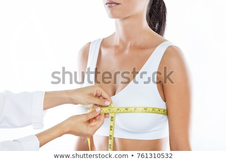 Woman measures breast by measurement tape. Stock photo © Nobilior