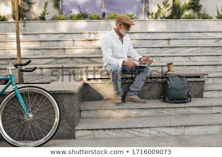 portrait of a young man with laptop outdoor sitting on bench stock photo © hasloo