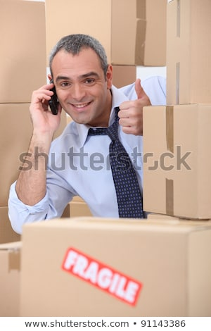 Happy man on phone behind stacks of boxes Stock photo © photography33