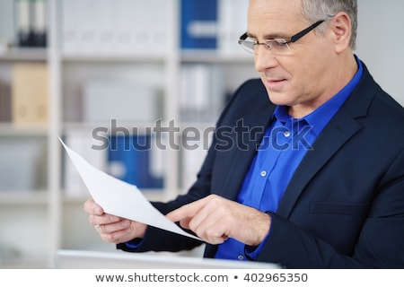 senior business man with reading glasses sitting at his desk Stock photo © feedough