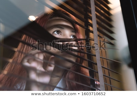 Attractive woman peeking through blinds Stock photo © stokkete