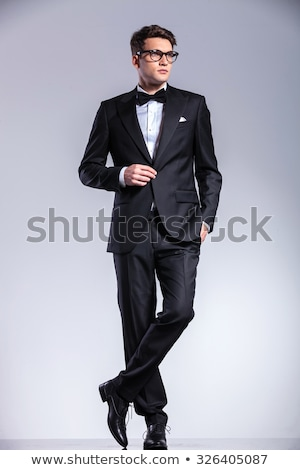 Happy young business man smiling while closing his jacket. Stock photo © feedough