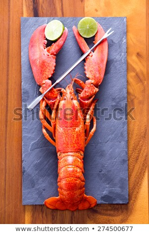 Stockfoto: Lobster Clipping Limes On Cutting Board With Picks