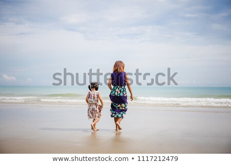 Happy family with little girl walk on beach in evening stock photo © Paha_L