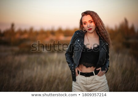 attractive woman walking in the fields with hands in pockets whi stock photo © feedough