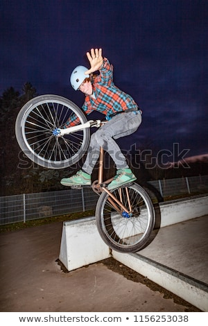 boy jumps with his dirtbike in the skate park over a ramp Stock photo © meinzahn
