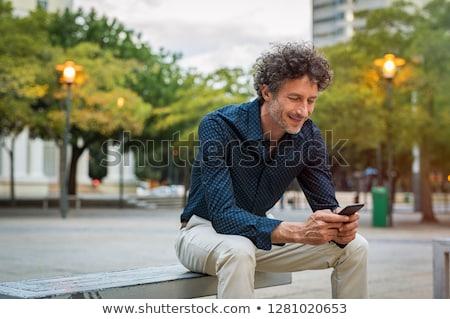 business man texting on evening outdoors stock photo © kzenon