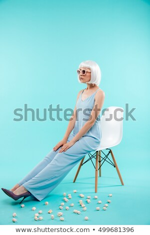 Woman in blonde wig and sunglasses sitting on the chair Stock photo © deandrobot