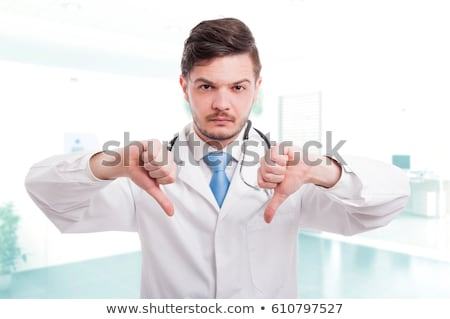 Disappointed caucasian doctor with thumb down Stock photo © RAStudio