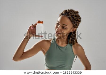 Sportsman standing over white background holding vitamins Stock photo © deandrobot