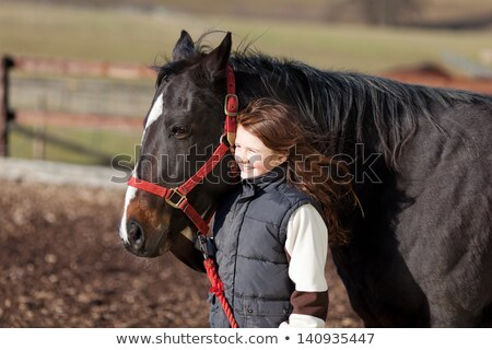 Stock photo: Smiling girl holding the rein of the horse in the ranch