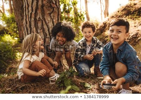 Többnemzetiségű barátok ül együtt park csoport Stock fotó © Kzenon