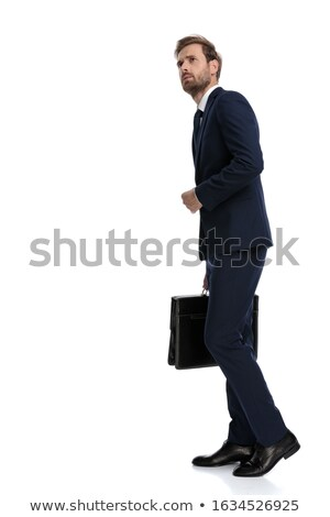 young curious businessman holds suitcase and looks to side stock photo © feedough
