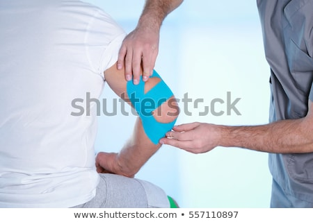 Physiotherapist Applying Kinesiology Tape On Patient's Elbow Stock photo © AndreyPopov