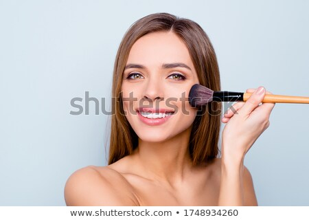 Pretty smiling woman doing photos. Isolated on gray background stock photo © studiolucky