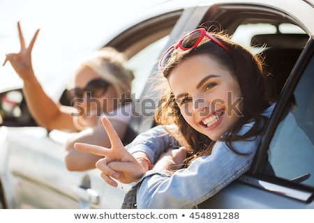smiling teenage girls showing peace in summer stock photo © dolgachov