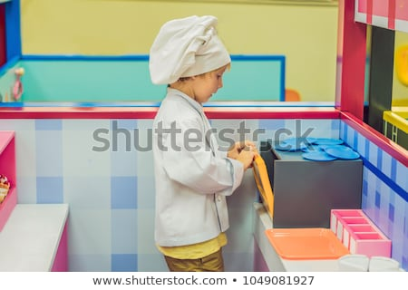 the boy plays the game as if he were a cook or a baker in a childrens kitchen stock photo © galitskaya