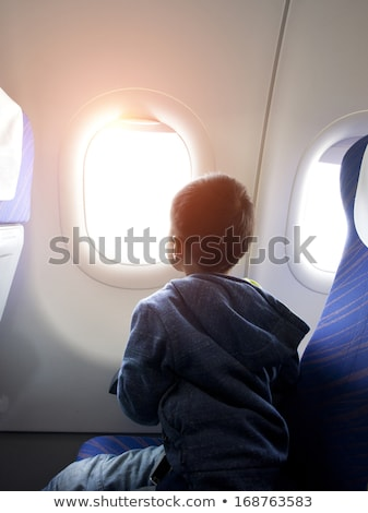 little boy in the plane looking out the window stock photo © galitskaya
