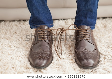Man tying shoelaces in living room at home Stock photo © wavebreak_media